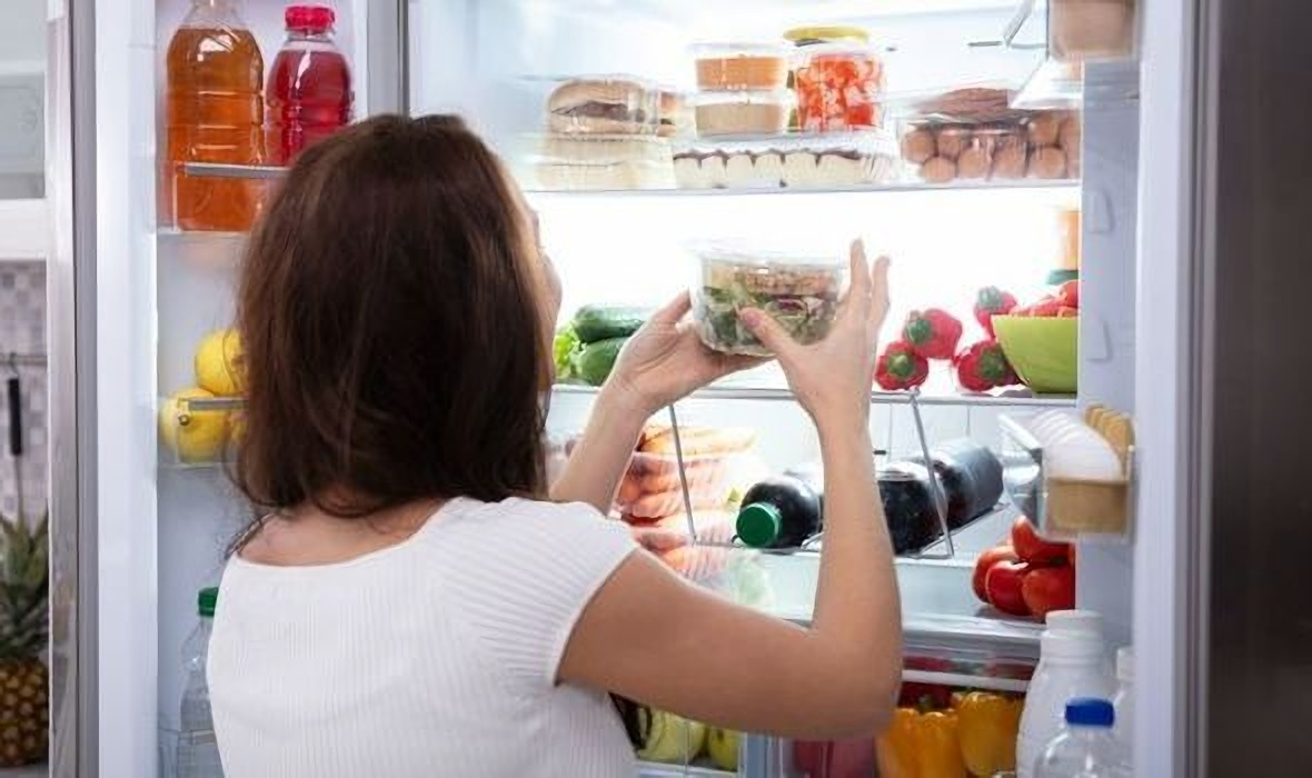 Seorang wanita sedang menata bahan makanan di kulkas