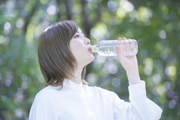 Seorang wanita sedang minum air mineral